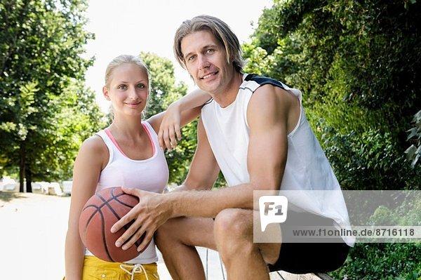Porträt eines Basketballpärchens bei einer Pause im Park