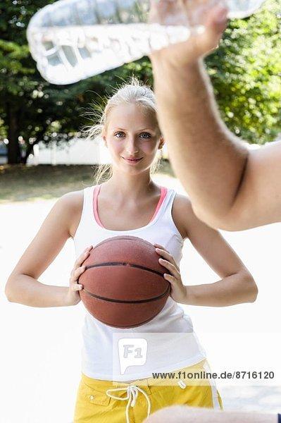 Junge Basketballerin macht Pause im Park