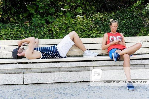 Zwei Basketballspieler bei einer Pause auf der Parkbank
