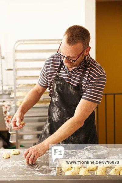 Bäcker  der den Teig in der Bäckerei formt