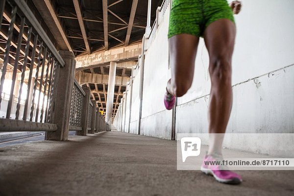 Cropped shot of young woman running on city bridge