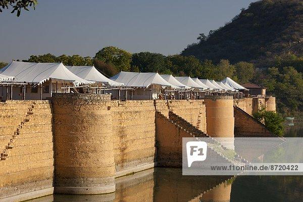 Chhatra Sagar reservoir and luxury tented camp oasis in the desert at Nimaj  Rajasthan  Northern India