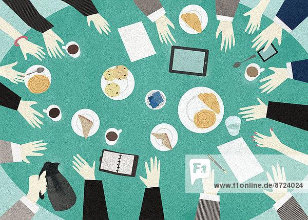 Draufsicht auf einen Tisch um den Geschäftsleute sich zum Frühstück treffen