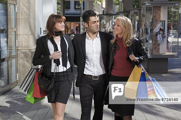 Young man and two young women  arm in arm with shopping bags  downtown  Hanover  Lower Saxony  Germany