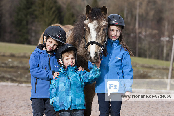Three children wearing riding helmets standing beside a pony  dun  with a bridle  Tyrol  Austria