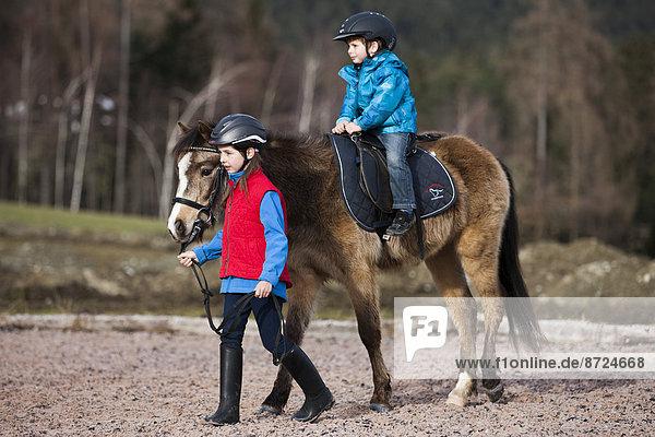 Mädchen führt ein Pony auf dem ein kleines Kind reitet  Falbe  mit Trense  Tirol  Österreich
