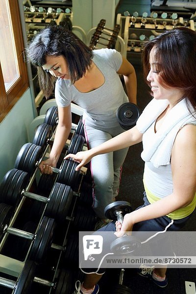 Two asian women choosing the right weight  Jakarta  Indonesia  Southeast Asia.
