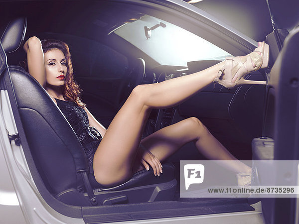 Junge sexy Frau sitzt im Auto  ein Bein aufgestellt
