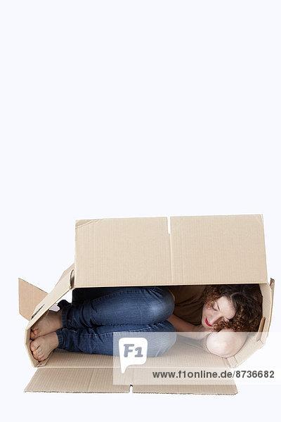 Junge Frau schläft in einem Umzugskarton