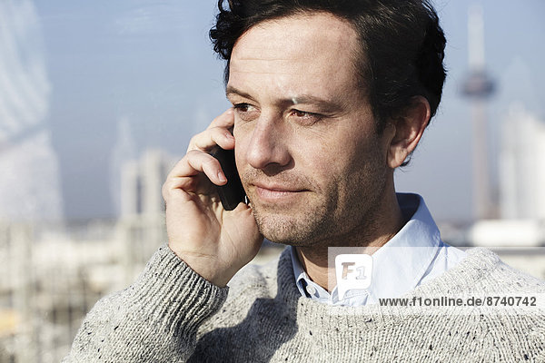 Germany  North Rhine-Westphalia   Cologne  portrait of man telephoning with smartphone