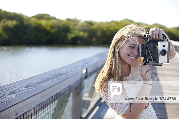Young Woman on walkway with Camera  Palm Beach Gardens  Palm Beach County  Florida  USA