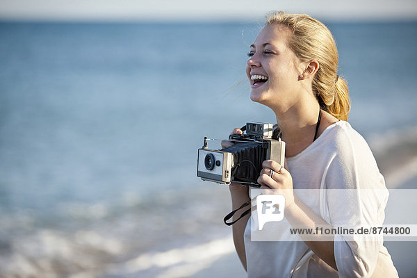 Young Woman Taking Pictures at Beach with Camera  Palm Beach Gardens  Palm Beach  Florida  USA