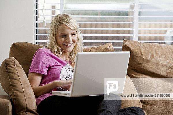 Interior  zu Hause  benutzen  Frau  Notebook  Couch  jung  Island