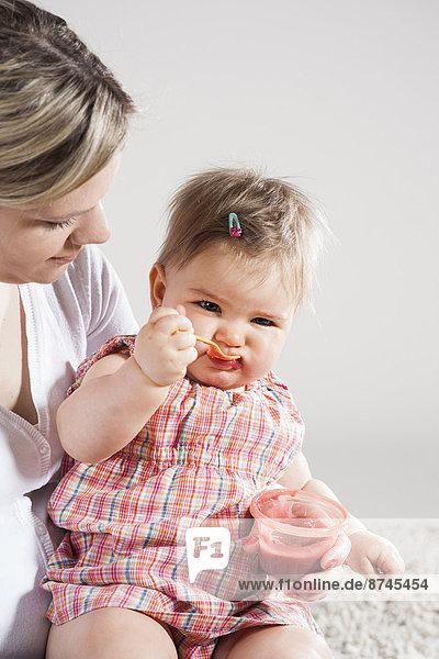 Studioaufnahme  Portrait  auf dem Schoß sitzen  Mädchen  Baby  füttern