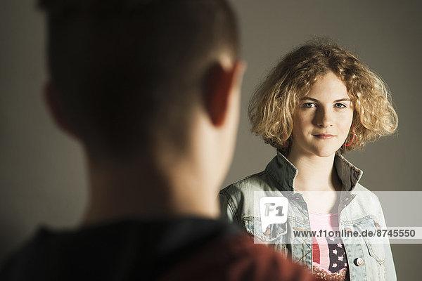 Teenage Girl looking at Teenage Boy  Studio Shot