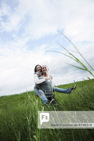 Frau  Mann  geben  fahren  reifer Erwachsene  reife Erwachsene  Feld  huckepack  Gras  Deutschland  mitfahren