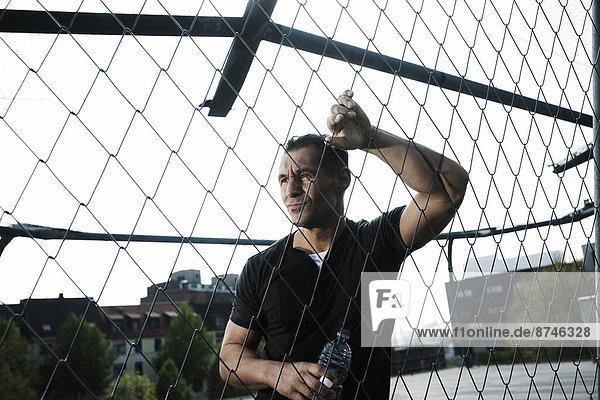 angelehnt  Mann  reifer Erwachsene  reife Erwachsene  Zaun  Basketball  Verbindungselement  Außenaufnahme  Verbindung  Gericht  Deutschland