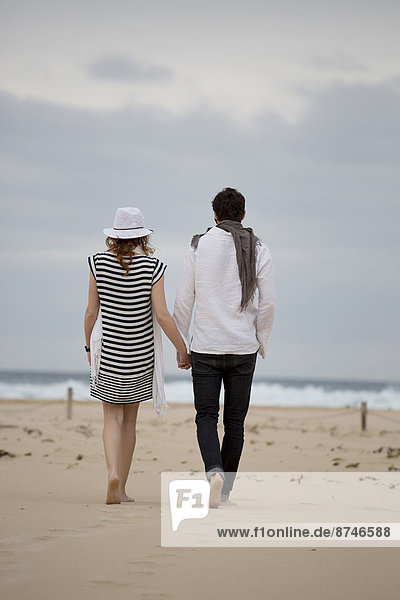 Back View of Couple Walking and Holding Hands on Beach  Sardinia  Italy