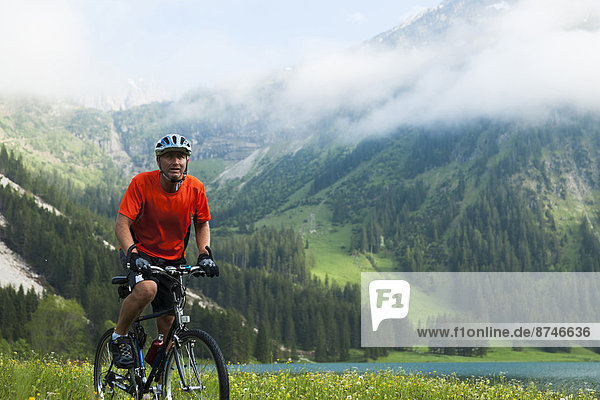 Mature Man Riding Mountain Bike by Vilsalpsee  Tannheim Valley  Tyrol  Austria