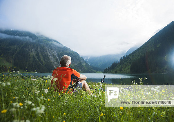 Mature Man with Mountain Bike sitting by Lake  Vilsalpsee  Tannheim Valley  Tyrol  Austria