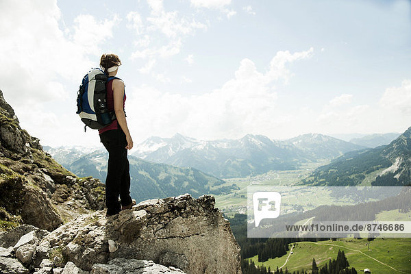 Mature woman standing on cliff  hiking in mountains  Tannheim Valley  Austria