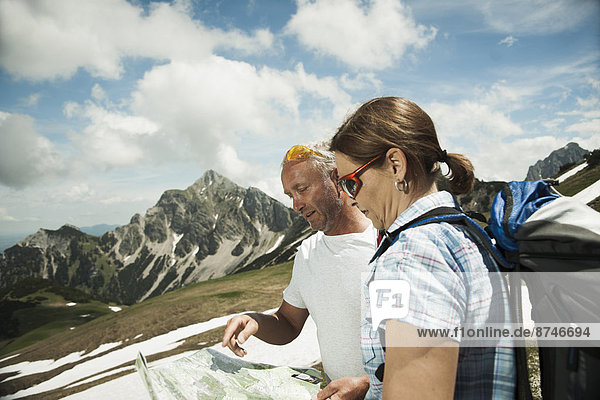 Mature couple looking at map  hiking in mountains  Tannheim Valley  Austria