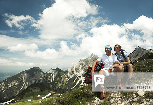 Mature couple sitting on grass  hiking in mountains  Tannheim Valley  Austria