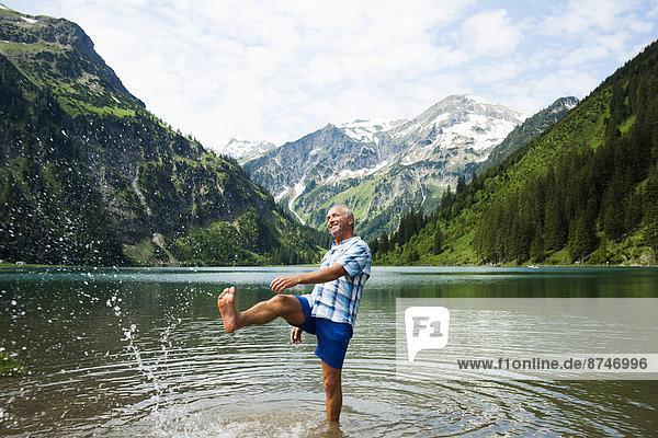 Mature man standing in lake  kicking water  Lake Vilsalpsee  Tannheim Valley  Austria
