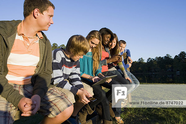 Group of pre-teens sitting on fence  looking at tablet computer and cellphones  outdoors  Florida  USA