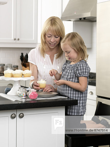 Mother and Daughter Decorating Cupcakes in open concept Kitchen  Toronto  Ontario  Canada