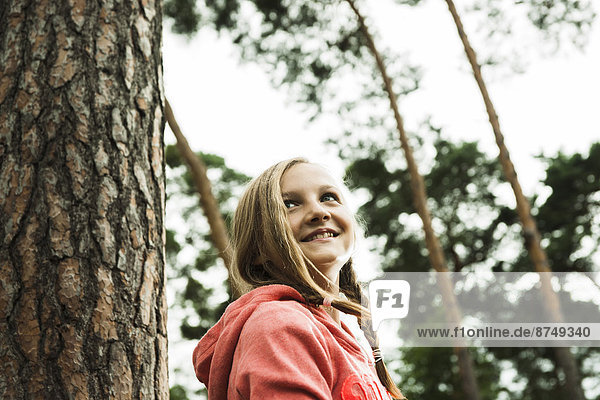Portrait of girl standing next to tree in park  looking upward  Germany