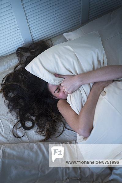 Frau  Enttäuschung  Hispanier  Bett  Kopfkissen  festhalten