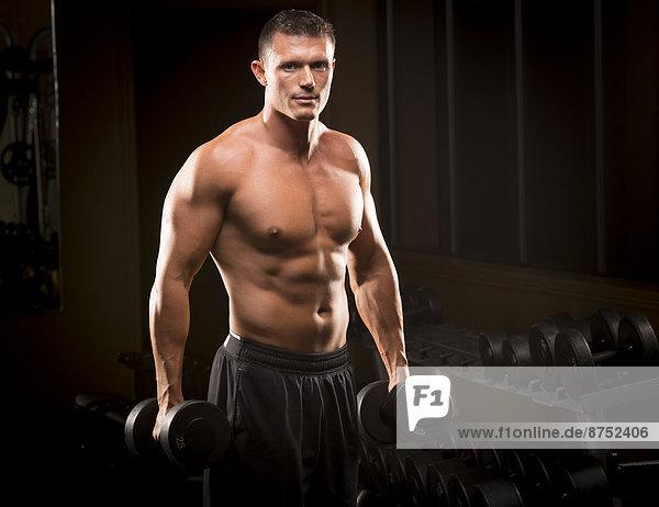 Confident Caucasian man holding dumbbells in gym