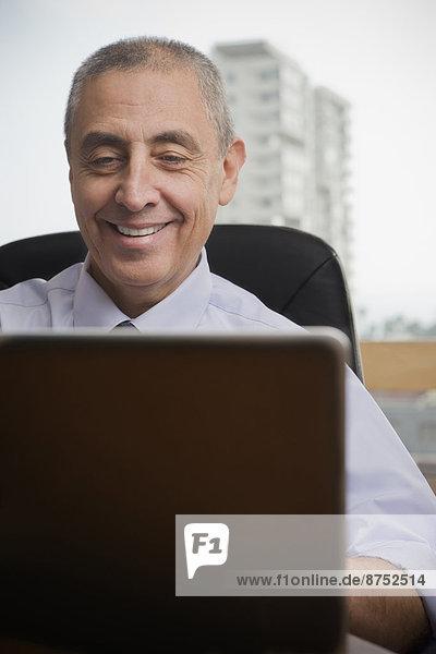 Close up of smiling Hispanic businessman using laptop