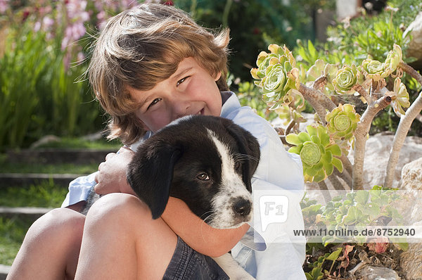 young boy with dog in garden