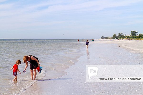 Florida  Sanibel Island  Gulf of Mexico  beach  beachcombers  woman  mother  boy  son  water  surf .
