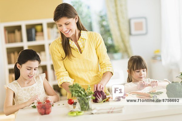 Mother and daughters (4-5 8-9) cooking in kitchen