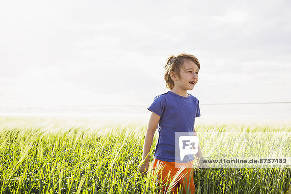 Boy (4-5) standing in grass and looking away
