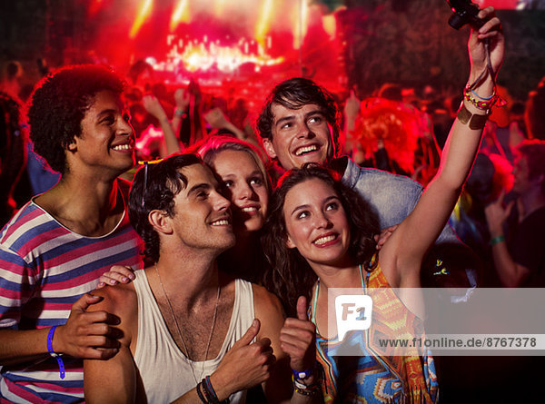 Friends taking self-portrait with camera phone at music festival