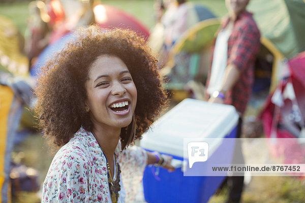 Porträt der lachenden Frau  die dem Mann hilft  kühlere Zelte auf dem Musikfestival zu tragen.