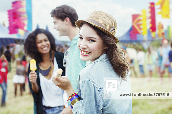 Porträt einer Frau  die mit Freunden beim Musikfestival Eis mit Geschmack isst.
