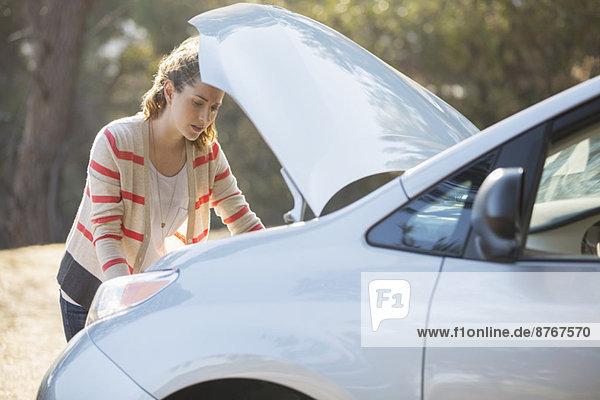 Frau überprüft den Motor am Straßenrand