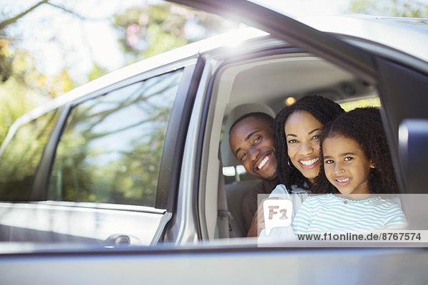 Porträt einer glücklichen Familie im Auto