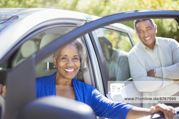 Porträt eines glücklichen älteren Paares innerhalb und außerhalb des Autos