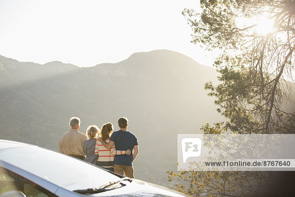 Familie mit Blick auf die Berge außerhalb des Autos