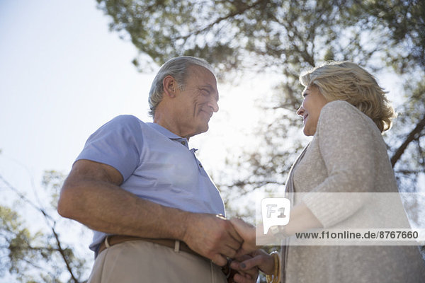 Glückliches älteres Paar hält sich an den Händen unter dem Baum