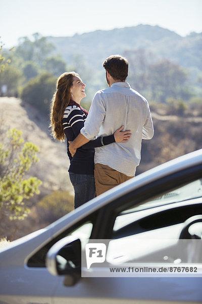 Glückliches Paar  das sich am Straßenrand außerhalb des Autos umarmt.