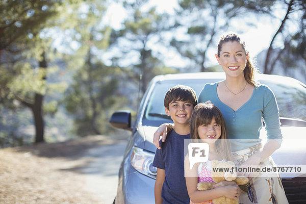 Porträt einer glücklichen Familie  die sich auf das Auto stützt.