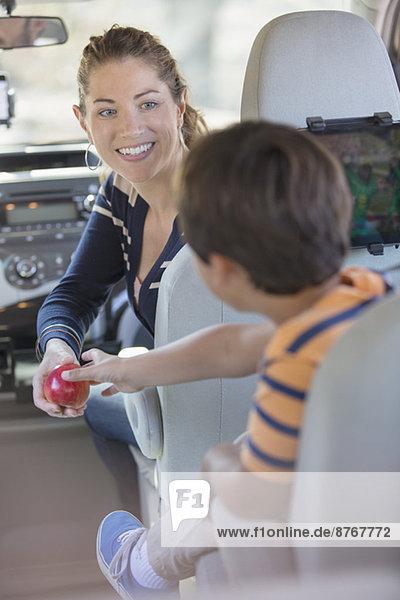 Mutter schenkt dem Jungen einen Apfel im Auto