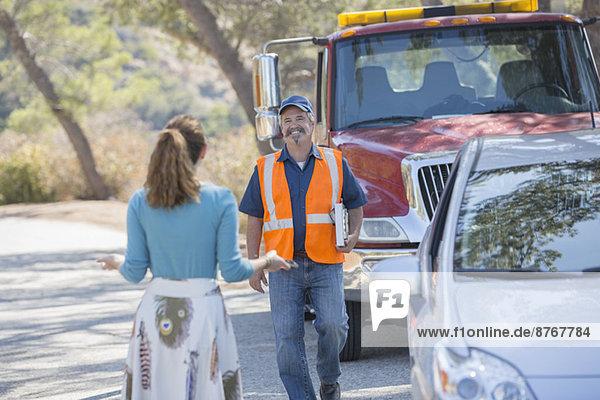 Frau begrüßt Mechanikerin am Straßenrand